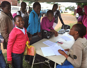 Photo: Ms. Zanele registering the arriving groups of double orphans.