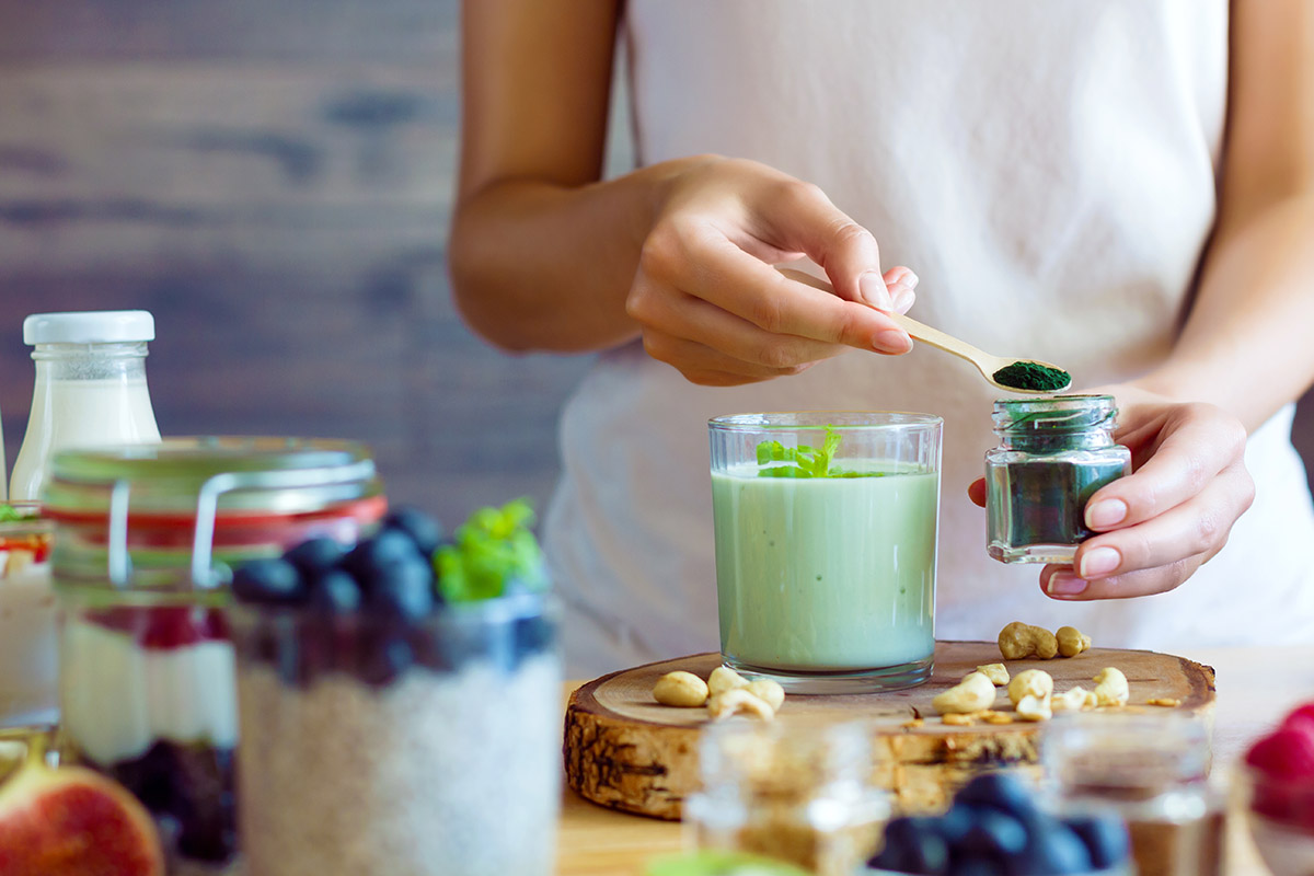 Whey Protein vs. Plant Protein:  Woman scooping green protein powder out of a glass jar