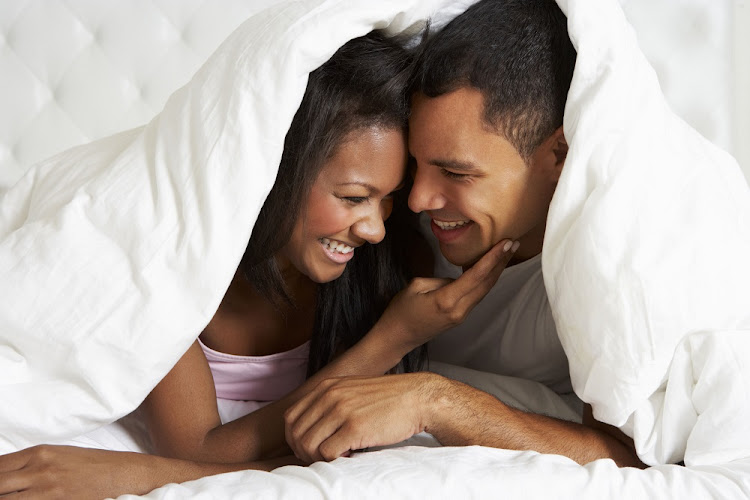 Couple Relaxing In Bed Hiding Under Duvet.