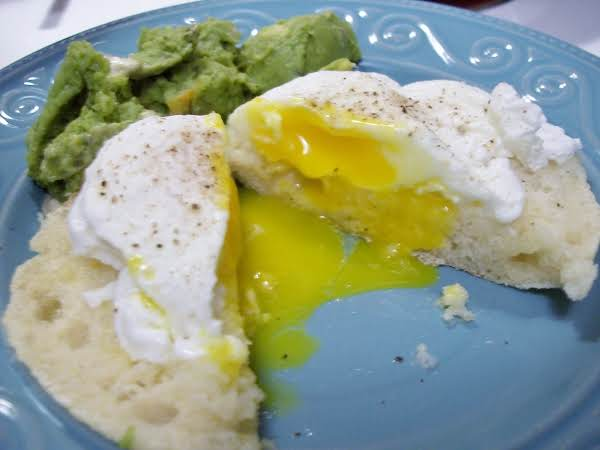 Poached Egg On English Muffin Cut In Half Showing Runny Yolk And With Mashed  Avocado.