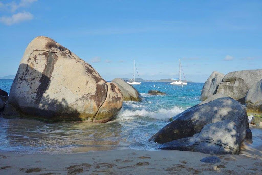 Baths_beach_Virgin_Gorda - Pleasure boats moor off a boulder-lined beach at The Baths on Virgin Gorda in the Caribbean.