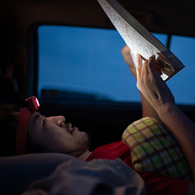 Yassan, laying in his car, checks his route on a paper map
