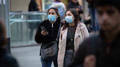 Dos mujeres por la calle con mascarillas.