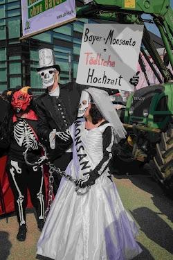 Protest-Show: Hochzeitspaar mit teuflischem Tod. «Bayer + Monsanto = Tödliche Hochzeit»