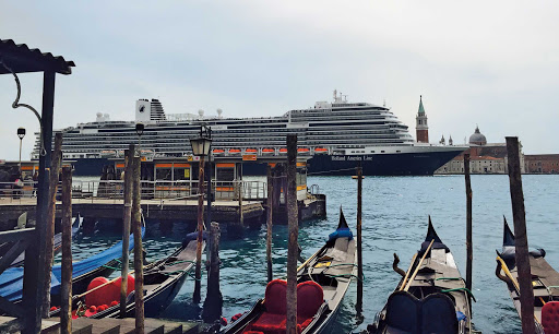 Gondolas bob in the Grand Canal as ms Koningsdam sails through Venice.