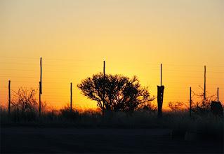 Photo: Zonsondergang met gamefence als symbool van het afscheid