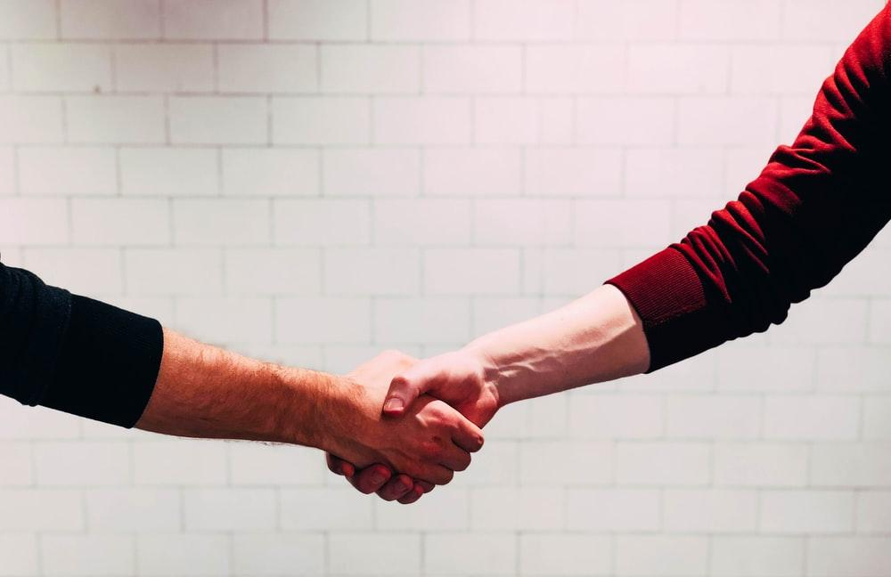白い塗られた壁の近くで握手する二人