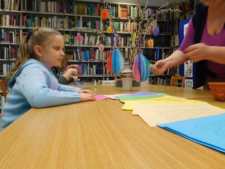 Papírt hajtogató gyermek a könyvtárban