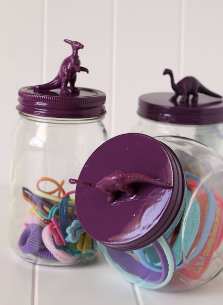 DIY Dinosaur Topped Jars make really cute kids bathroom decor. Fill them up with adhesive bandages, hair accessories, jewelry, cotton swabs - whatever your kids (or you!) use regularly
