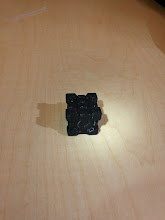 """Photo: Our first object, a 1"""" Companion Cube ( http://www.thingiverse.com/thing:13588) printed in MakerGear provided Black PLA.   Slic3r tells me it took2430.0mm (5.8cm^3) of filament, which are obvious lies and not consistent when multipled by the cross-section of the filament. The actual time was around 45 minutes (~10 less than estimated, not sure why.  Came out pretty well, bottom was a tad smushed (my inadequate tramming), the skirt was lightly fused to the print, and the top was a little rough (known to be hard with that model)."""