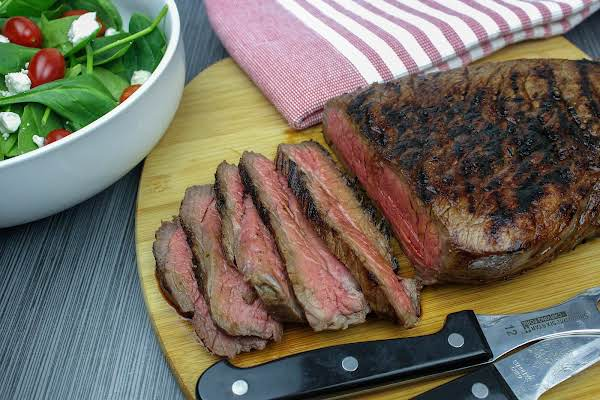 London Broil Sliced On A Cutting Board With A Salad.