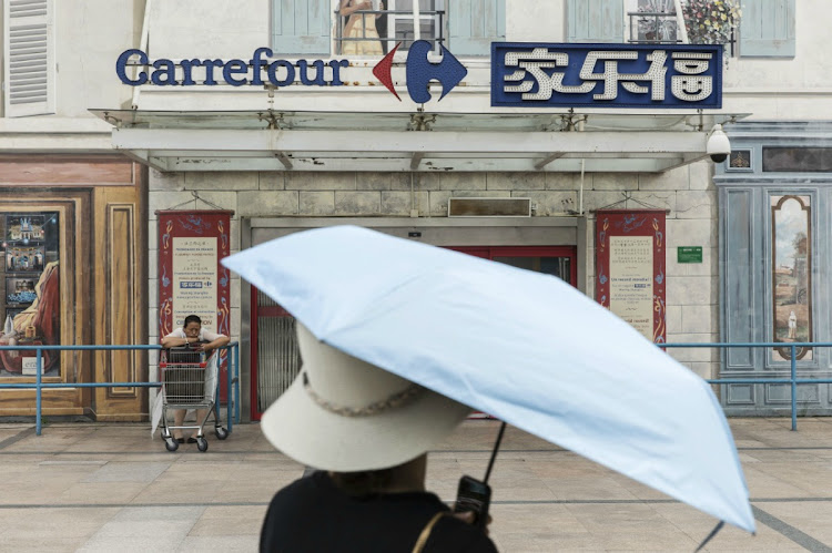 2f4a26b1c642a A pedestrian walks past a Carrefour SA supermarket in Shanghai, China, in  Monday,