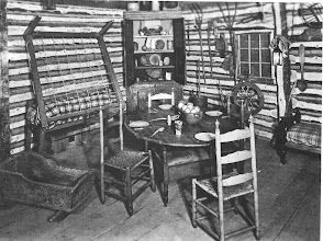 Photo: Another view of the Onondaga cabin showing a turned up bed. The table in the center of the room would be turned  up into a bench during the day. You can make out the seat underneath.