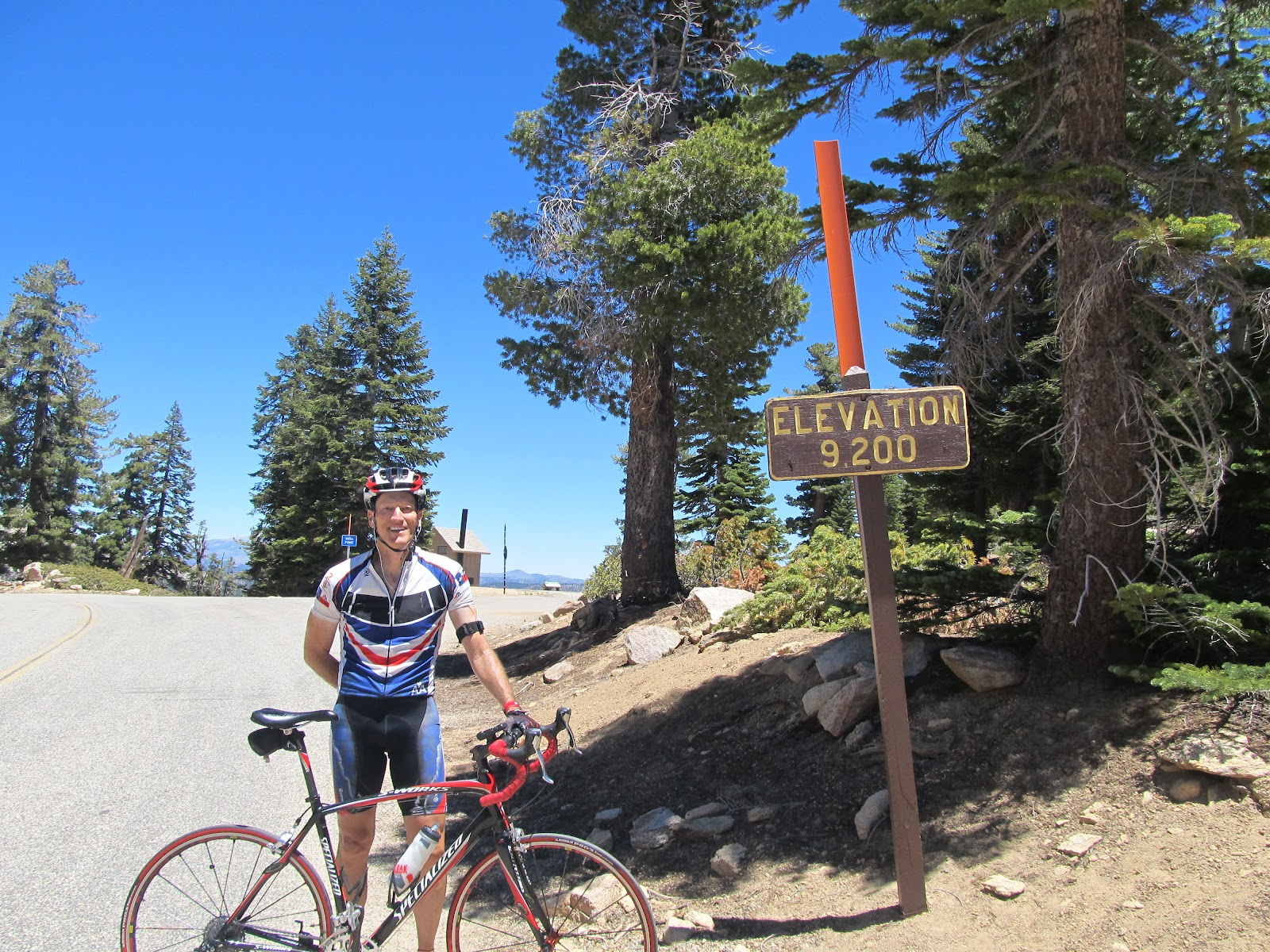 Climbing Sherman Pass by bike - elevation sign and cyclist with bike.