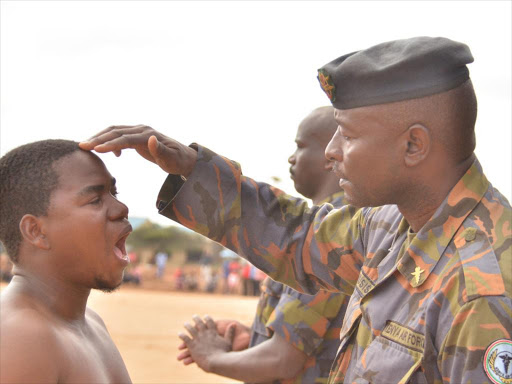A KDF soldier examines a prospective recruit during the recruitment drive at the Hola Stadium, November 23, 2018. /ALPHONCE GARI