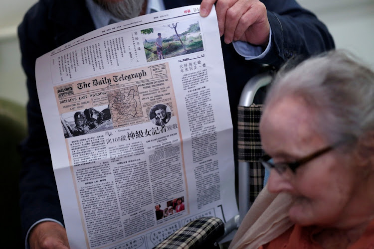 A friend holds up a story on the late British journalist Clare Hollingworth at her 105th birthday in Hong Kong, China. Picture: REUTERS/BOBBY YIP