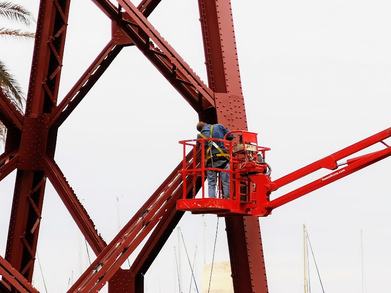 Un operario trabaja en las alturas sobre la estructura metálica.