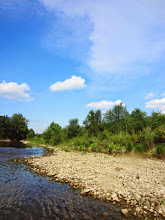 Photo: River and rocky beach under bright blue skies at Eastwood Park in Dayton, Ohio.