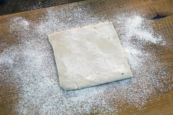 Lightly flour a work surface and then cut the puff pastry into 4-inch squares.