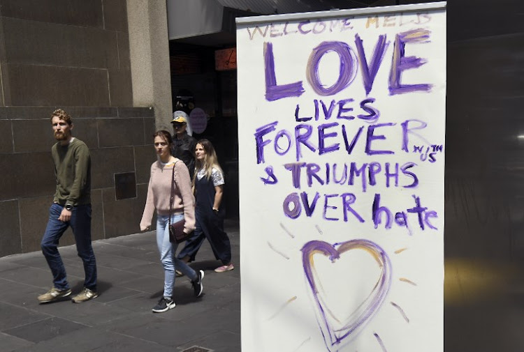 People walk past a sign at the scene where a man was killed in the November 9 knife rampage, in Melbourne on November 10, 2018.