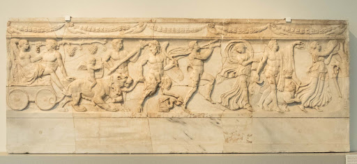 This slab covered a sarcophagus-like grave in a wall, depicting a procession with the Greek god and princess in a panther chariot led by satyrs and maenads, dating to 110-130 A.D. at the Altes Museum in Berlin.