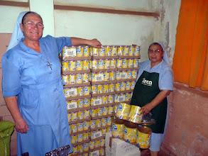 Photo: Soeurs Séréna et Assunta posent souriantes devant le riz au lait Mont-Blanc de notre container de décembre 09