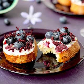 Blueberry Chevre Crostini with Champagne Vinegar Hibiscus Flowers.
