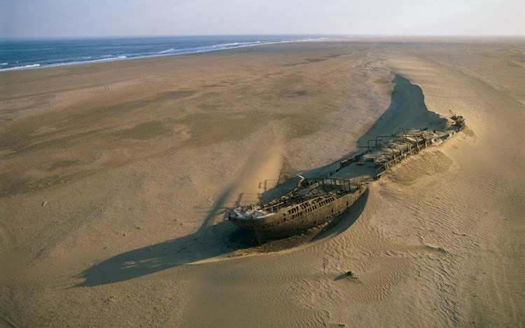 A lone wreck is slowly swallowed by the sands along the Skeleton Coast