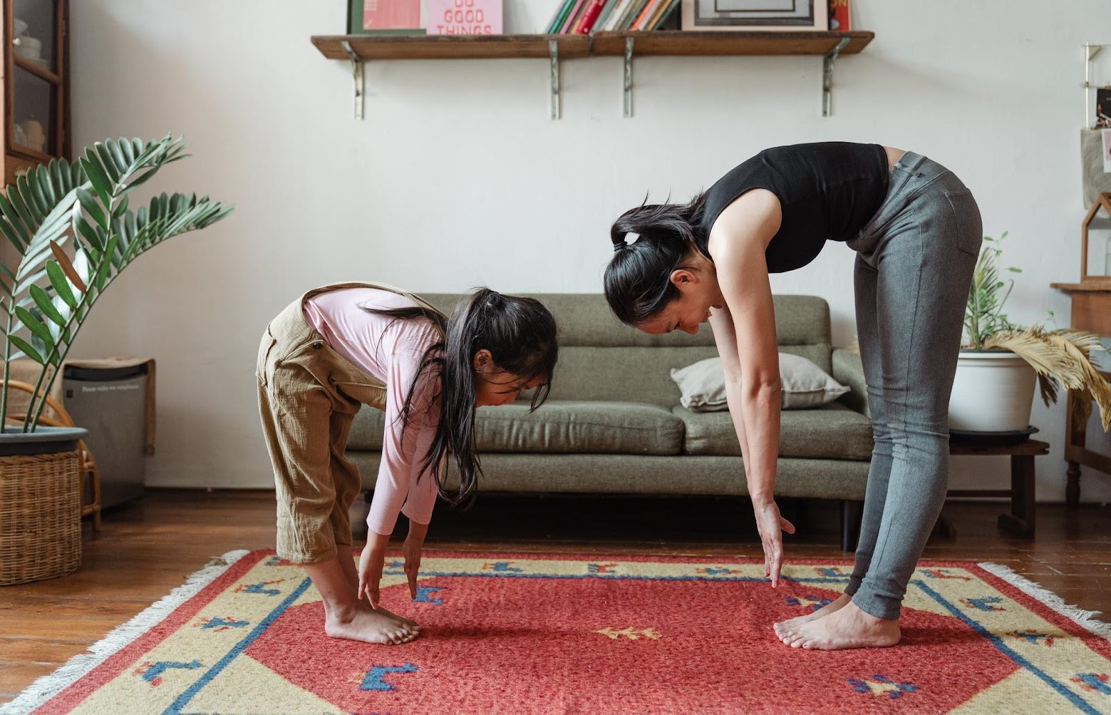 Mother and child stretching together in a stylish living room.