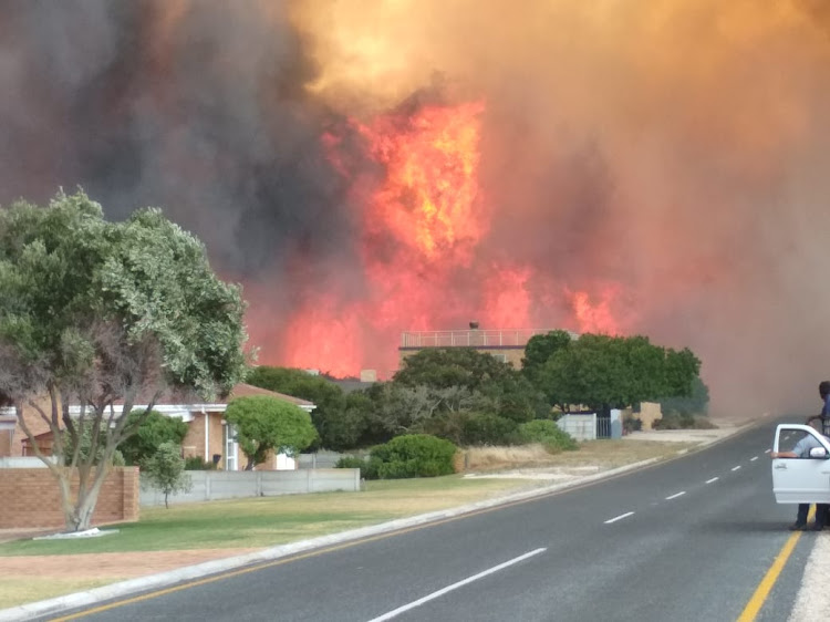 Flames roar behind a house in Franskraal, near Gansbaai on the Western Cape's Overstrand coast, on Friday January 11 2019.