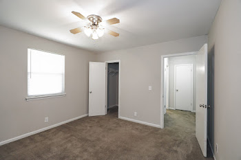 Bedroom with brown carpet and light walls and ceiling fan