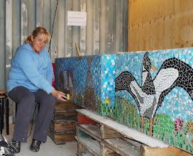 Photo: Monique Klaasen aan het werk aan de mozaïekbankjes die bij Columbuzz geplaatst zijn