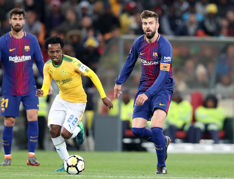 Mamelodi Sundowns' star forward Percy Tau dribbles away from Barcelona's Gerald Pique during the Nelson Mandela Centenary Cup friendly match at FNB Stadium, Johannesburg on May 16 2018.