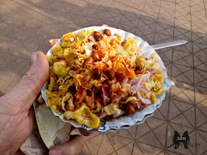 """Photo: BHEL PURI  Indian Street Food   Crunchy Flavourful and Spicy Bhubaneswar India Bhel-puri is a savoury chaat variant involves puffed rice or Lai/muri as main ingredient which is flavored variously with chutneys, spices and few other ingredients like boiled potatoes, peanuts, plantain, onions, tomatoes, green chillies, sev etc. Bhel Puri is sold in paper cones or disposable leaf bowls.  Bhel Puri is thought to be originated in Gujarati Cafes or in street food stalls of Mumbai. The perfect balance of sweet, tart and savory flavors. In Mumbai/Bombay it is called """"Bhel"""", in Kolkata, it is called Jhal-Muri, in Odisha it is Jhal- Mudhi and in Bangalore it has got name """"Churmuri""""."""
