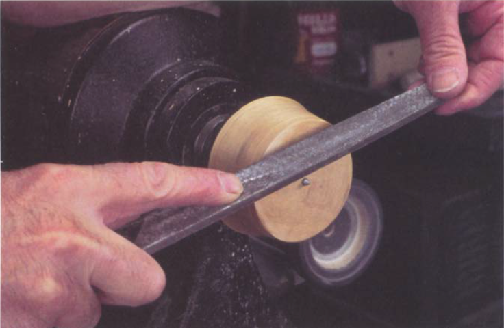 To prepare for pressure turning. file the nail protruding from the glue block to a point.