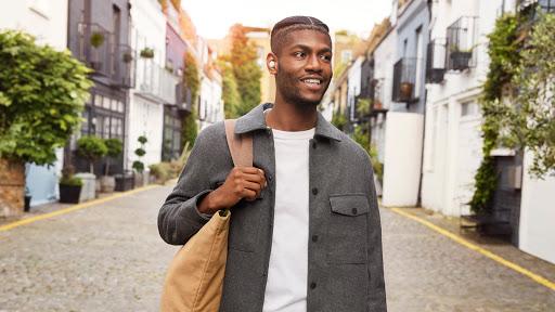 """Un joven camina con una bolsa color marrón al hombro. Dice """"Hey Google"""" a sus Pixel Buds A-Series para preguntarles cómo se llega a la heladería que hay de camino a su casa."""