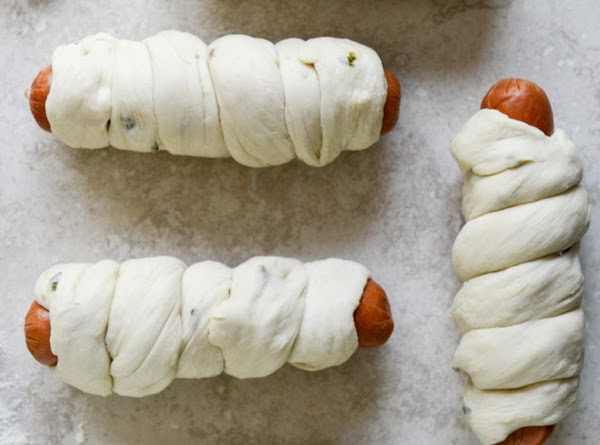Wrap each strip of dough around the hot dog, starting a the bottom.