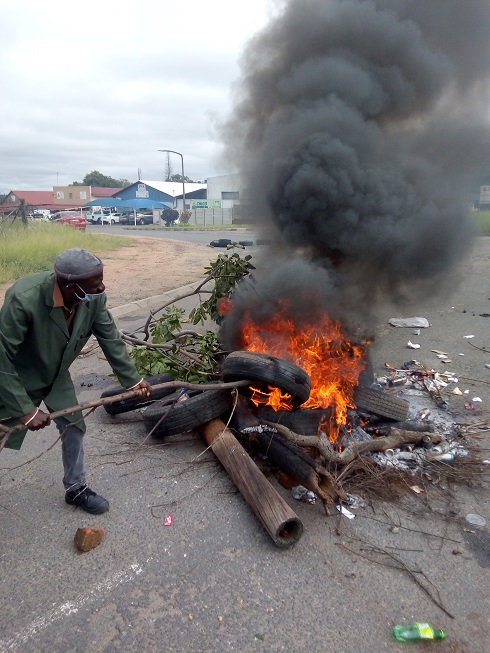 A member of the Ba-Phalaborwa Community Forum adds fuel to the fire as protesters demonstrate outside a Foskor mine in Limpopo on Wednesday.