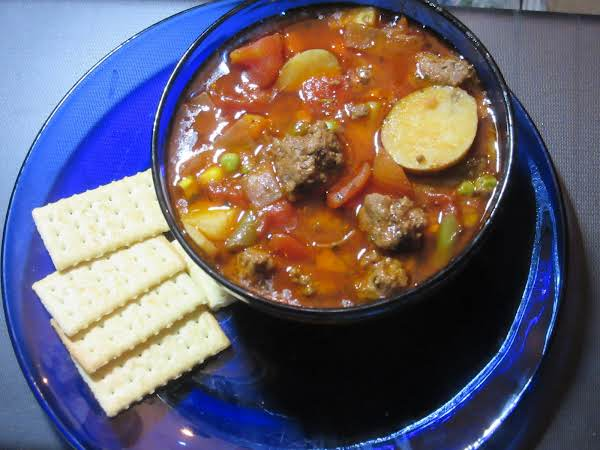 Vegetable Soup In A Blue Bowl With Crackers On A Blue Dinner Plate.
