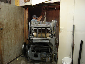Photo: The Miehle was the most difficult piece of equipment to move out of the basement. Here Loren is using a chain hoist bolted into the concrete above to swing the press onto the special platform he made to pull the press up the stairs.