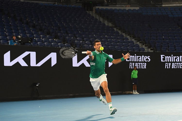 Novak Djokovic of Serbia plays a forehand infront of an empty stand in his Men's Singles third round match against Taylor Fritz of the United Statesduring day five of the 2021 Australian Open at Melbourne Park on February 12, 2021 in Melbourne, Australia.