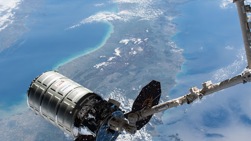 The Cygnus resupply ship is in the grips of the Canadarm2 robotic arm prior to its installation to the Unity module at the International Space Station.