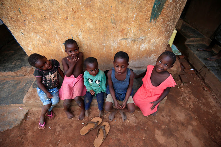 Some of Mariam Nabatanzi's children rest on the verandah at their home in Kasawo village, Mukono district, east of Kampala, Uganda, on March 8 2019.