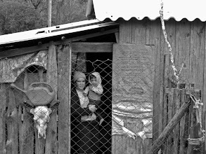 Photo: A mother and son peer through a wired fence at the entrance of their modest home.
