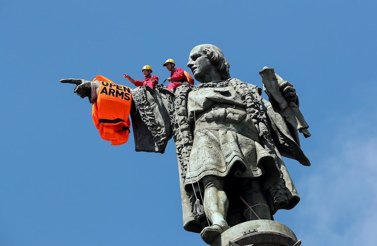 Activists from the Spanish Proactiva Open Arms charity place a life jacket on the Christopher Columbus statue after the Open Arms rescue boat arrived at a port in Barcelona, carrying migrants rescued off Libya.