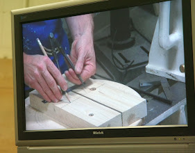 Photo: We'll need a frame to hold the partly-turned bowl blank straight and firmly for the hollowing operation.  Mark marks a pair of 2 x 4s to make a custom saddle.  Note the excellent utility of our new video monitor.