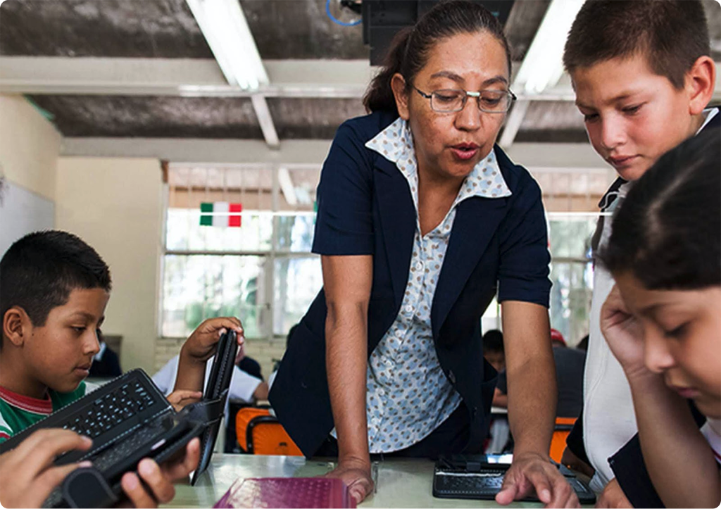 Una maestra que enseña a varios niños pequeños a usar un dispositivo.