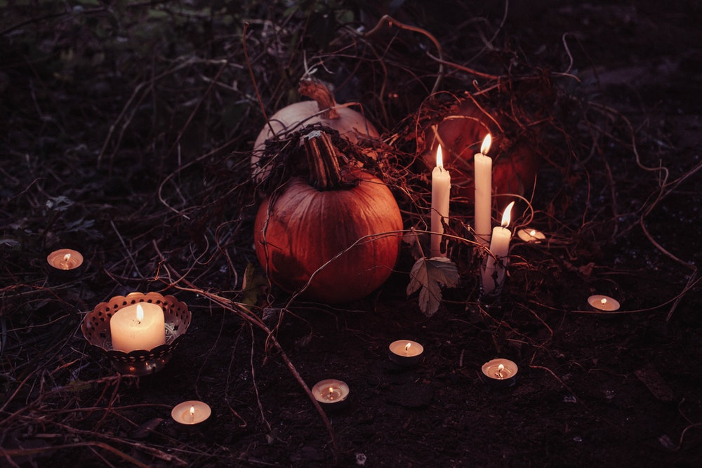 Pumpkins with branches on the ground with lit candles by them in Barcelo
