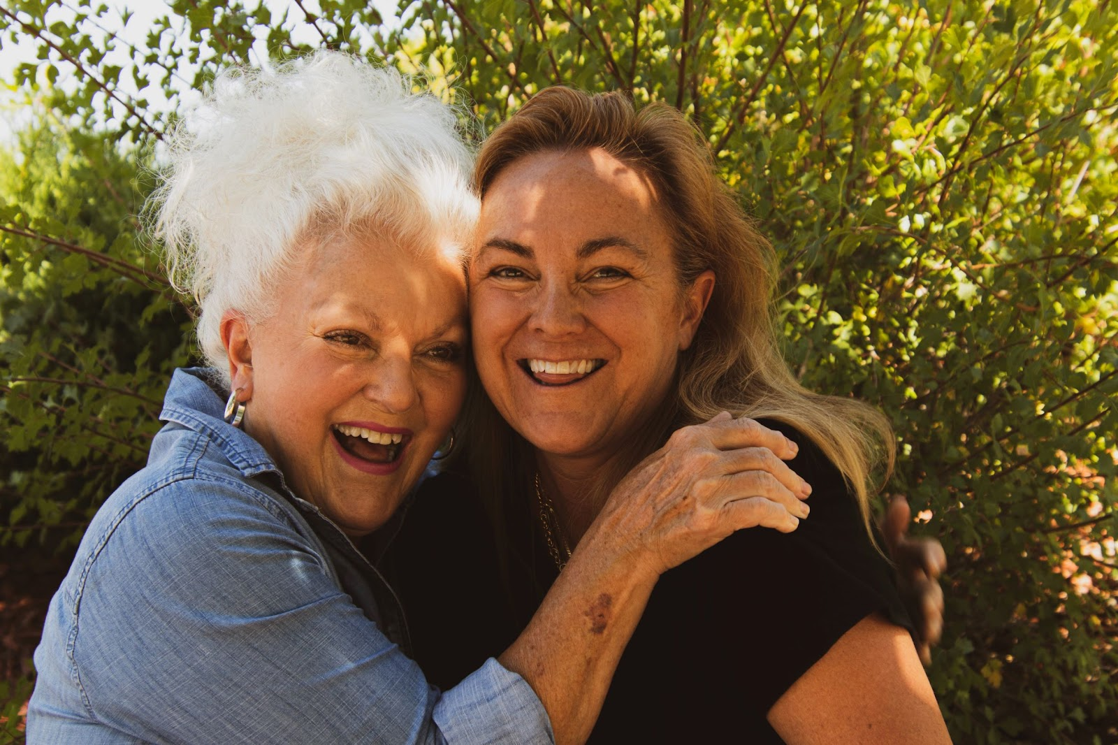 Two older woman hugging by a tree