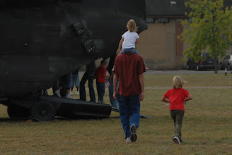 Photo: A family walks to see a CH-47 Chinook helicopter.